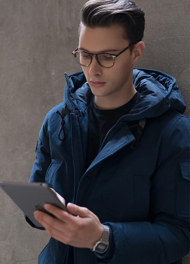 Man with EyeBuyDirect blue light blocking glasses and tablet