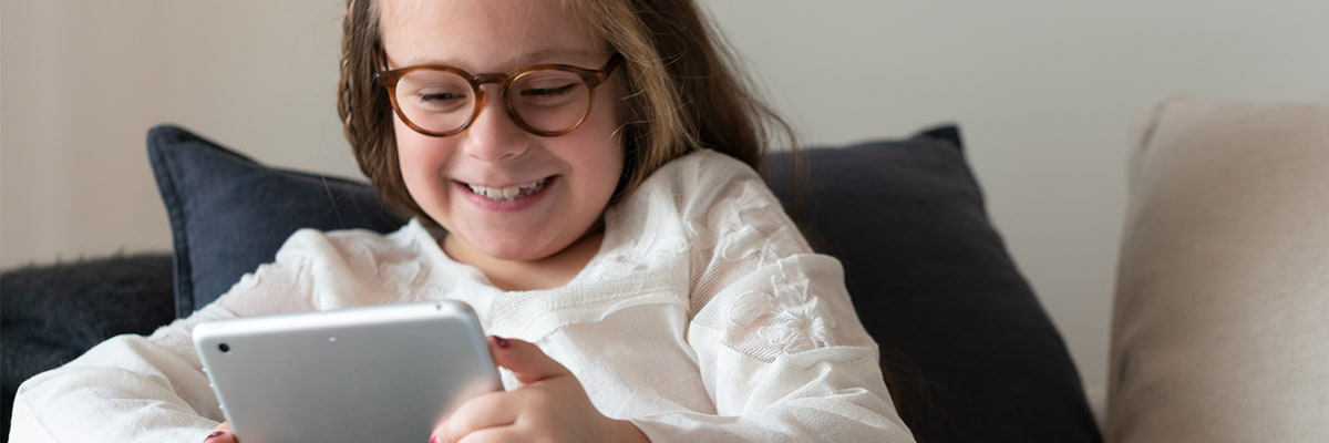 A child wearing glasses looking at a tablet