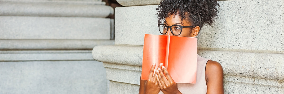 A woman wearing glasses holding a book in front of her face