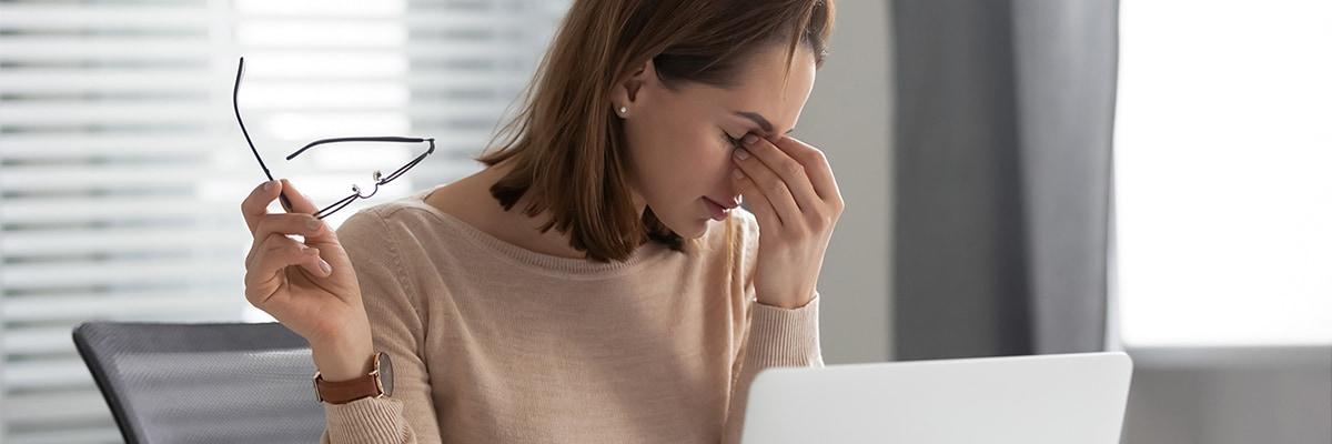 A woman using a laptop suffering from a headache
